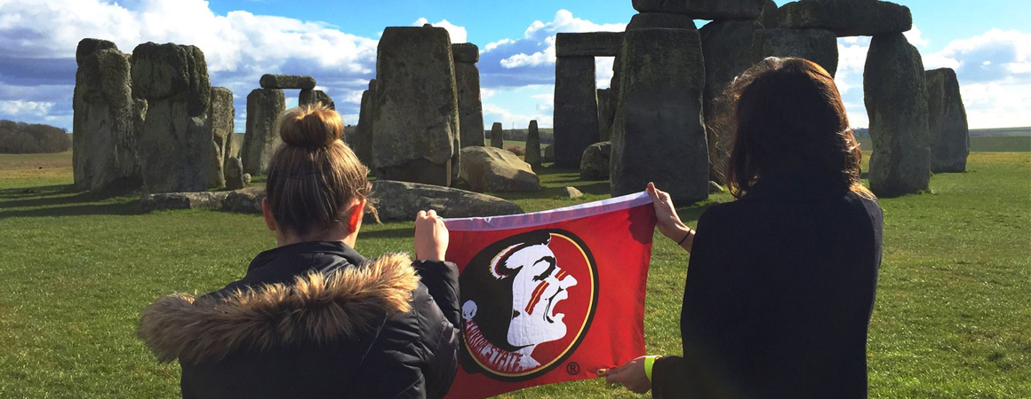 Students holding an FSU flag at Stonehenge
